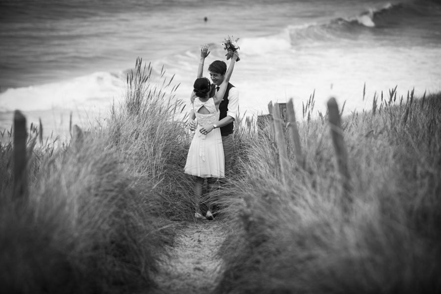 Copy of Bride and groom embrace on beach