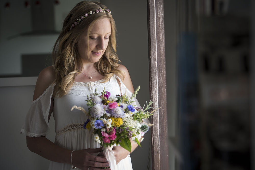 Bride with window light and bouquet at boho cornwall.jpg