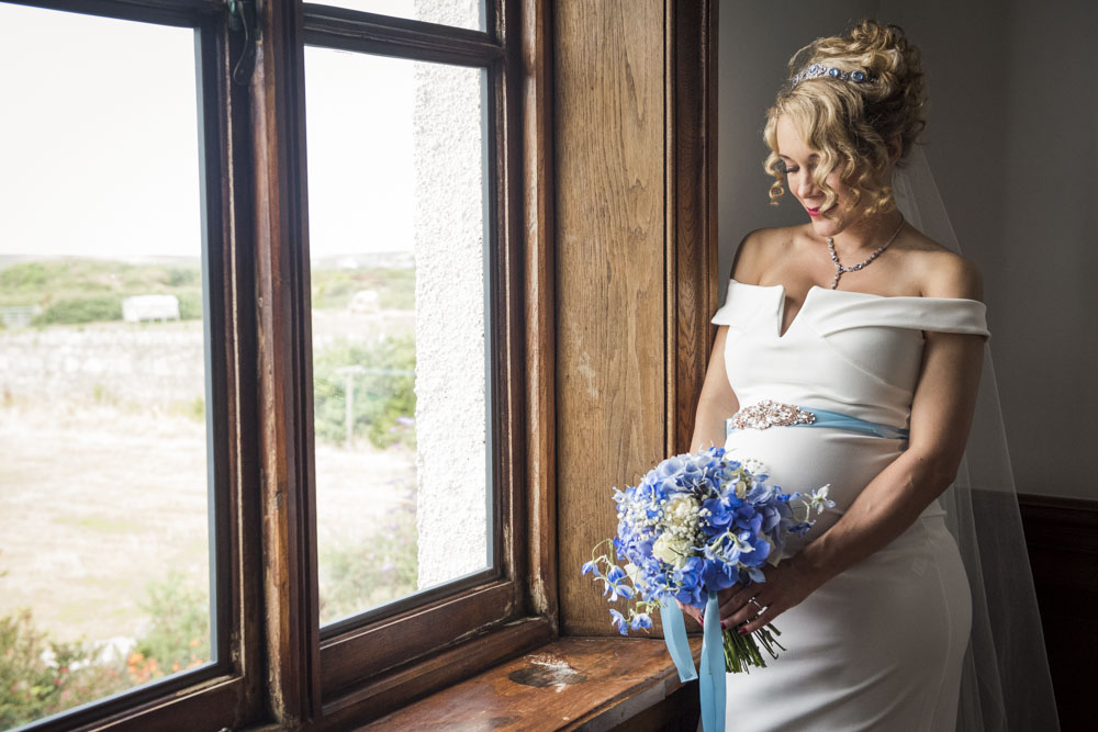 bride with flowers by window boho cornwall.jpg