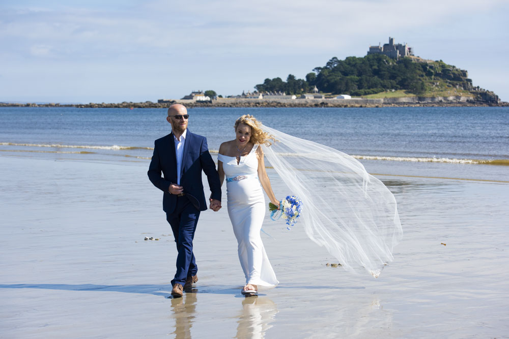 bride and groom walk on the beach at Marazion.jpg