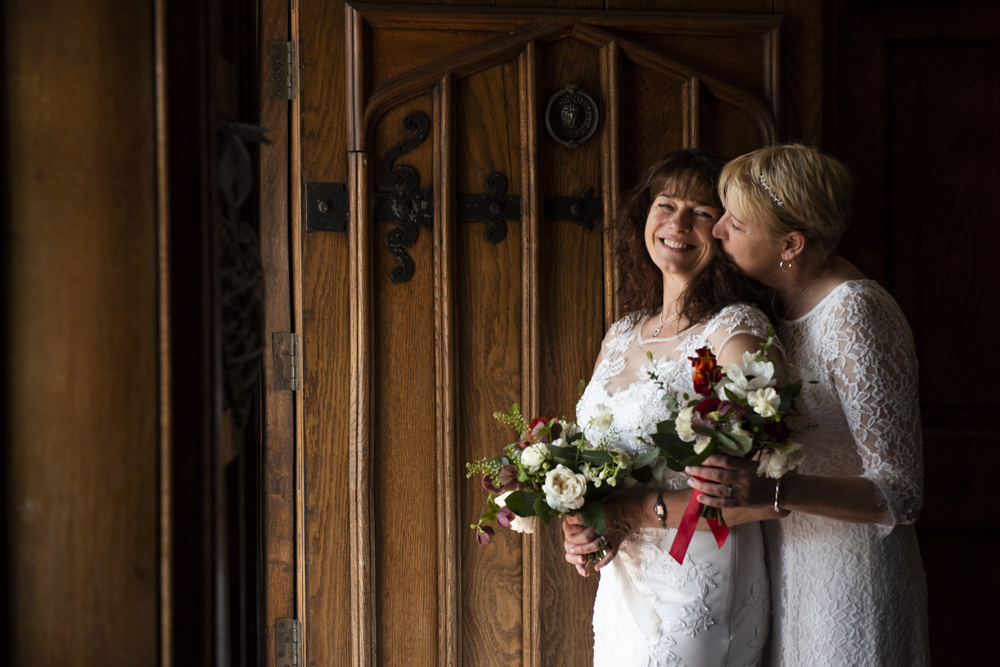 Lesbian brides by door at boho cornwall