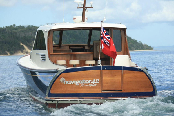 The stern view of the Navigator 42 is impressive, with its full teak fit out, classic helm, and large electronic drop down window which creates an open bulkhead and bar area, making this boat the perfect entertainer or family launch.