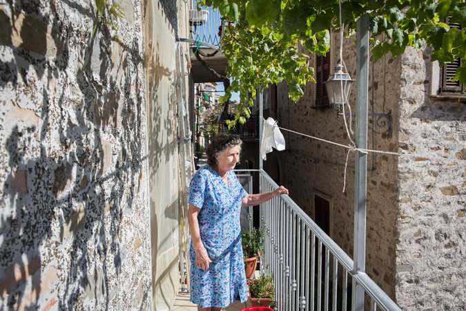 enisia La Greca, 82, growing fruit and vegetables in her garden.     CreditGianni Cipriano for The New York Times