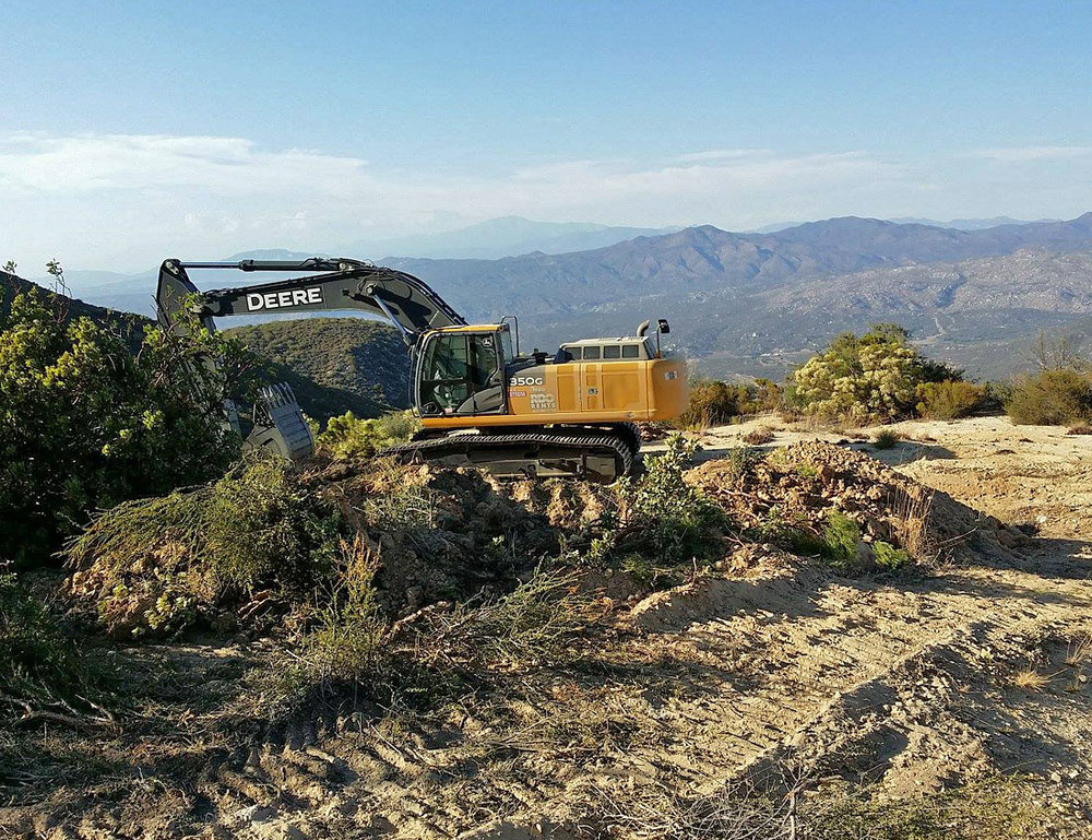 The Deere clears out brush in preparation for the pegmatite exposure. Click to enlarge. (Photo: Casey Jones)