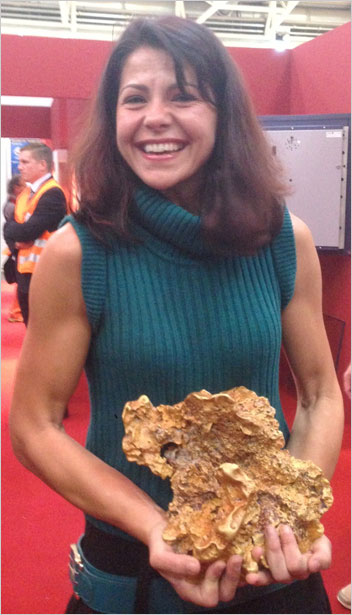 "Gold's Gym. Dr. Raquel Alonso-Perez, Curator of the Harvard Mineralogical & Geological Museum, will present ""Over 200 Years of the Harvard Mineral Collection"" on Collector Day at this year's Westward Look Show. Above, she achieves muscle tone with a hefty gold specimen at last year's Munich Mineral Show. (Photo: Bill Larson)"