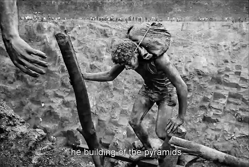 From the trailer for The Salt of the Earth: having climbed a series of ladders, this worker emerges from the gold mine pit with a bag that could pay off.