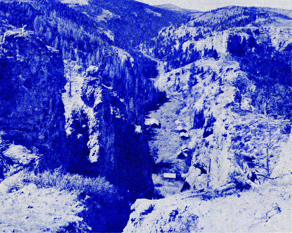Figure 4.—View westward into the mouth of Kelly Gulch from the crest of the east wall of Yogo Gulch. Dumps of old mine workings may be seen along the northern margin of the valley floor behind the row of deserted houses. Judith Basin County, Mont.