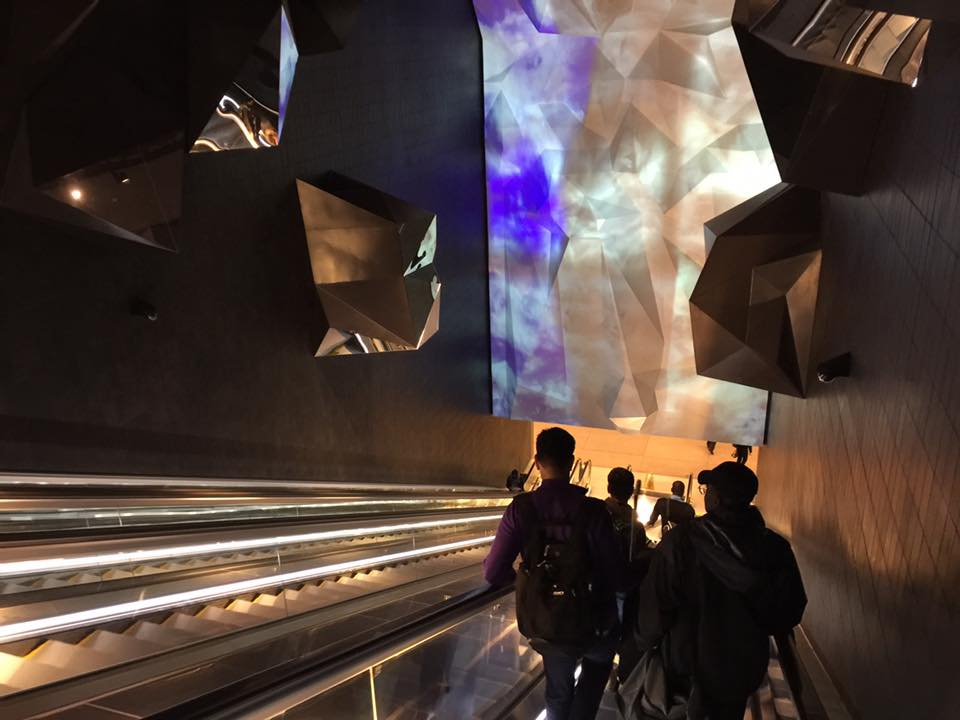 In transit(ion).  The projection moves from sky-blue to powder-white as travelers descend the escalator. Rock-like prominences jut from the walls, reflecting the light. Fact: all the A Line trains at the bottom of this people-mover have built-in retractable snow plows. (Photo: Eric Verlo)