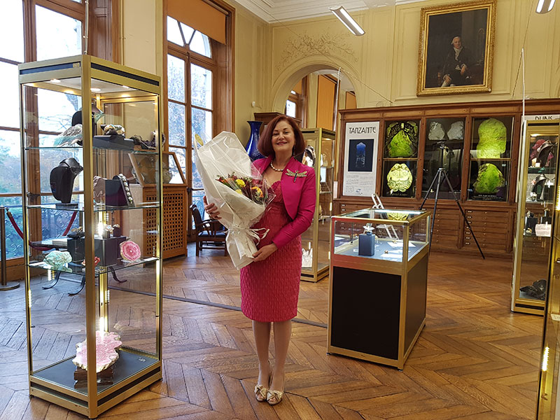 Paula Crevoshay stands amidst her own creations as well as those of Mother Earth in the exhibition hall prior to the opening of  Illuminations: Earth to Jewel . Over her shoulder is a poster of the tanzanite specimen pictured below, as well as a painting of Balthazar Georges Sage, first director of the School of Mines, 1783–1790. (Photo: Farida Maouche, MINES ParisTech)
