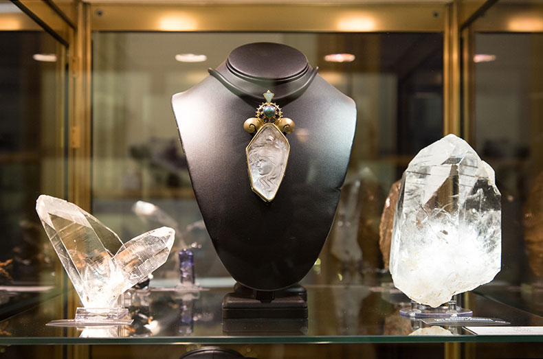 """Actual display of Paula Crevoshay's framing of Thomas McPhee's 173.16-carat carved quartz,  """"Maia,""""  flanked by a Japan Law twin from La Gardette Mine in the Rhône-Alpes region of eastern France and another massive quartz. (Photo: Thibaud Vaerman, MINES ParisTech)"""