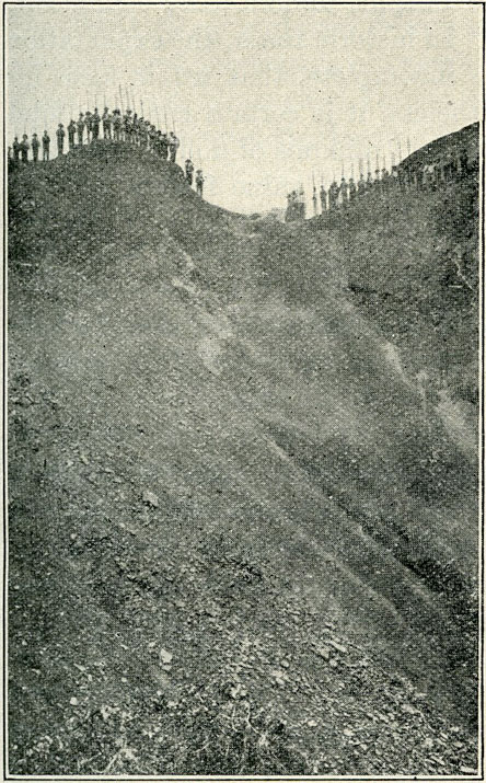Photograph showing how accumulated débris is cleared from working face by water let in from above. The miners on the ridge hold their work implements—long, iron crowbars with which they break down the emerald formations.