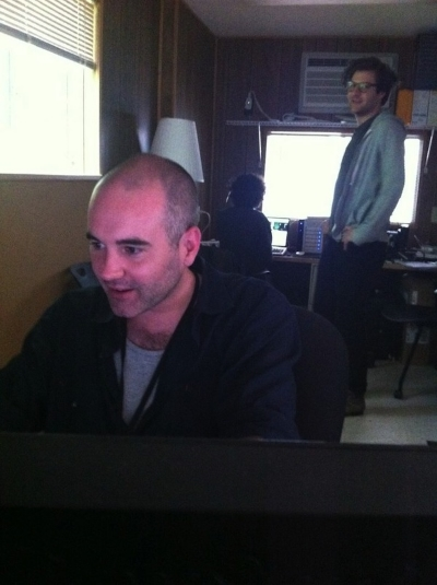 Andrew looks on as Jim problem-solves at his work station.