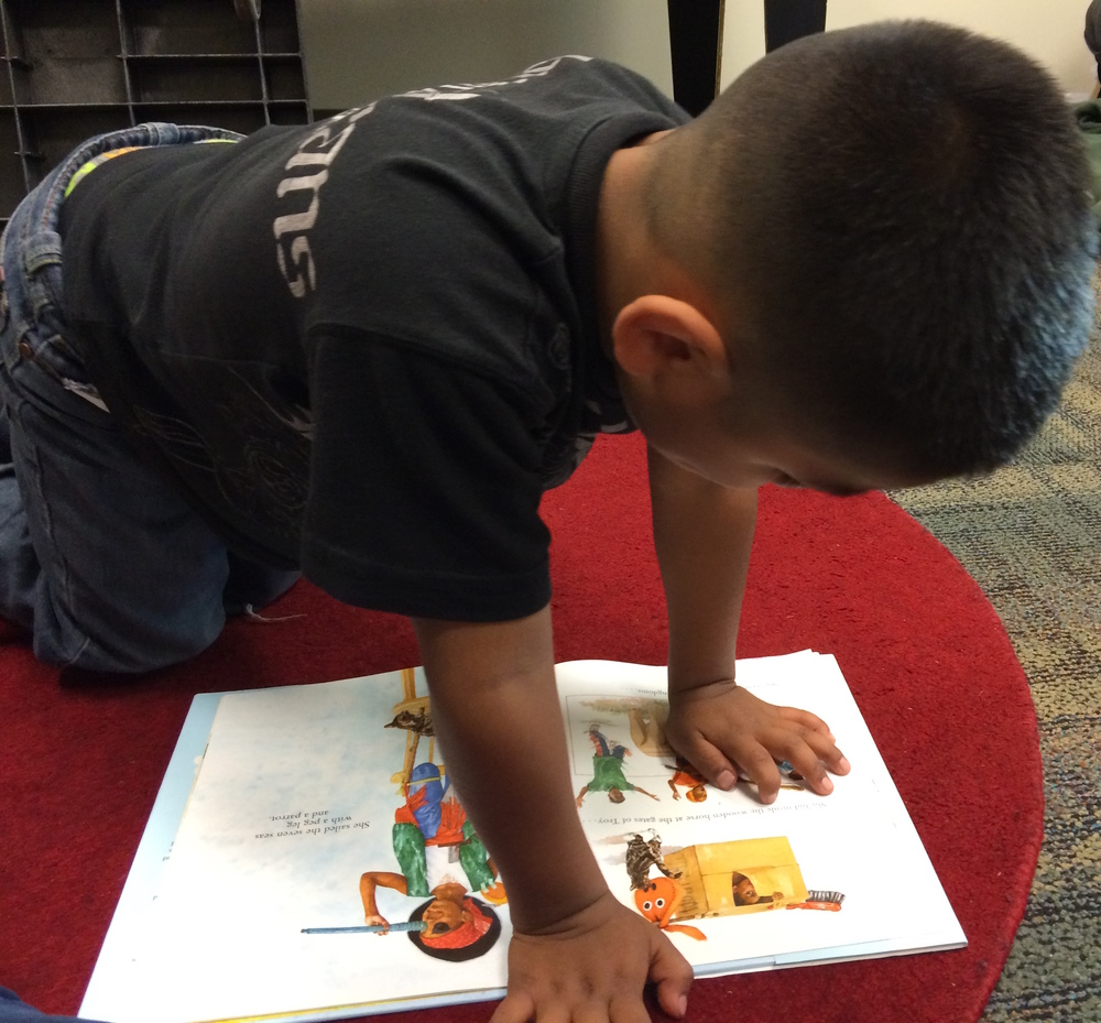 A Bright Start student reads his monthly book.