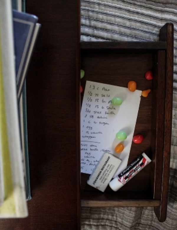 A secret look into my bed-top desk drawer: a recipe card, matches, chapstick, and a few stray jelly beans