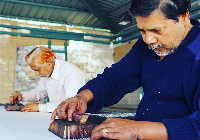 Master woodblock printers focused on their craft. Woodblock printing really is a labor of love. #woodblock #woodblockprinting #craft #India #printing #art #travelphotography #travel #lifeote #lifeovertheedge