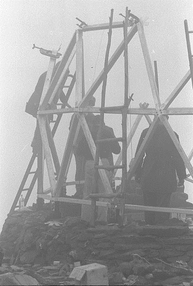 "The third level of joints being assembled. The joint ""stars"" were clamped on with G Clamps and moved around until the horizontal and vertical angles (as well as the radius) were correct. This was done quite accurately. I remember this day was so foggy that we could not line up the theodolite with the trig station on Mt Fainter so the theodolite was moved around until the angles to the existing joints all were correct. This took an hour or so and when the sun burnt off the fog and I turned the telescope to where the trig station should have been it was not visible. Then I realized that it was behind the vertical target line of the telescope. Max Cory who had just returned from an 800 mile traverse in Antartica as a surveyor simply didn't believe it either. From then on we put several reference targets near the hut so that we could easily line up with those points even in the fog."