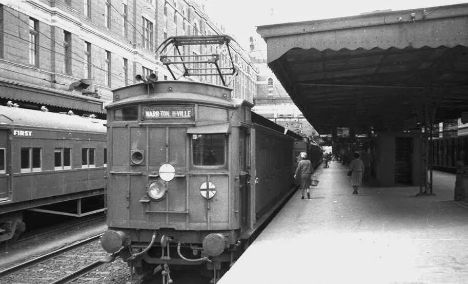 An E-Train at Flinders Street Station.  The 'Swing Door' (also known as   'Dog Box'   ) electric cars at the front towed the country carriages to the suburban terminus at Lilydale, where a steam engine took over for the second half of the journey.  Photographer unknown.