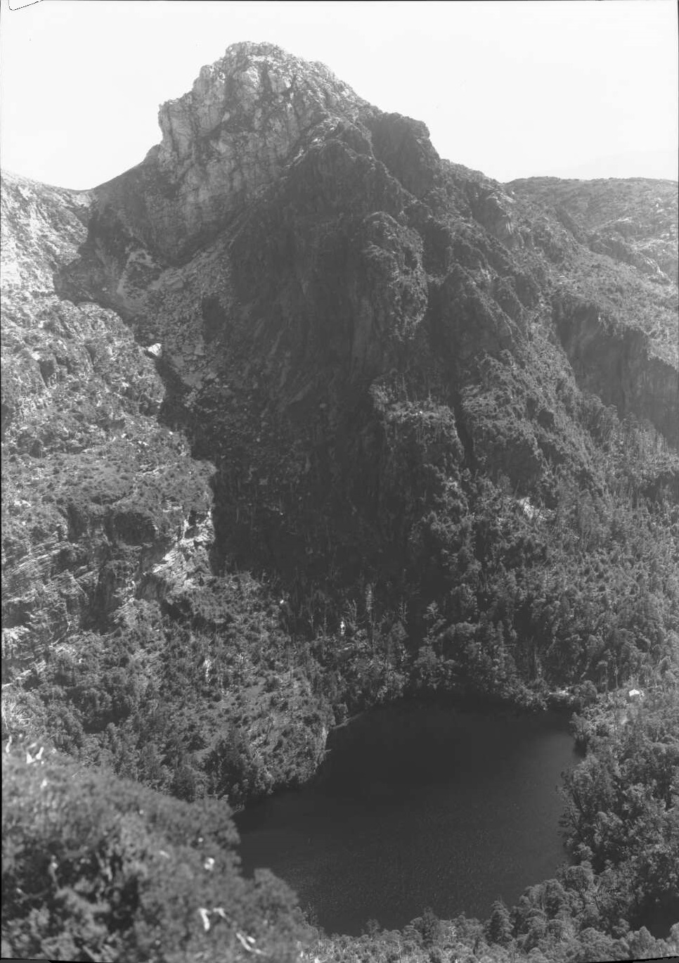 Frank Hurley's photo of Lake Tahune in 1947. Lions Head towers above the lake while the face of Frenchmans Cap is to the left of this scene. Source: National Library of Australia.