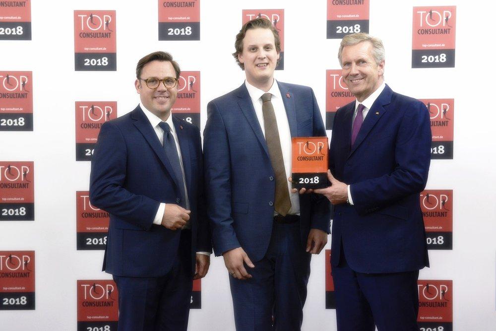 Dr. Christian Höfeler und Carsten Speckamp, dchp®, mit Bundespräsident a. D. Christian Wulf bei der Preisverleihung zum Top-Consultant (Foto KD Busch/compamedia)