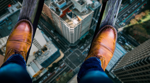 Photo 1st person point of view, looking down at shoes and down at city streets below while standing on two thin planks of wood