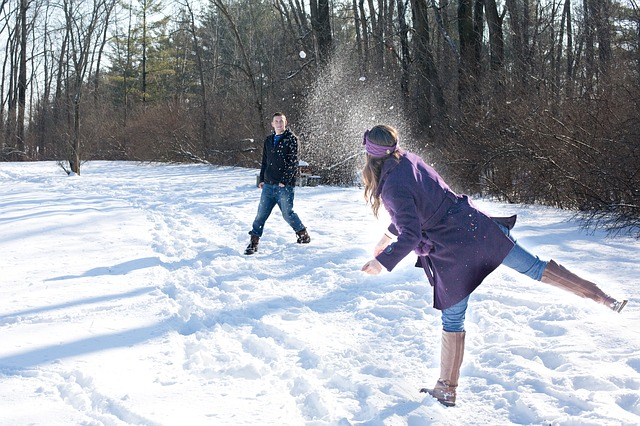 Photo of man and woman having a snowball fight
