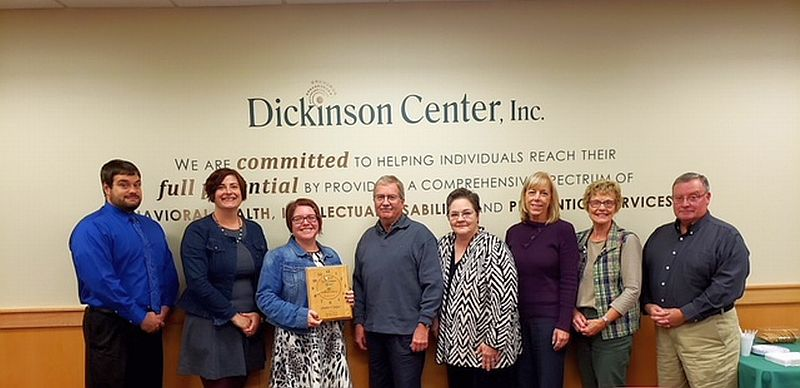 "Amber Cooper, LCSW, (3rd from left) holds the 2018 ""Sis"" Simons Memorial Award plaque with Dickinson Center Board members, pictured from the left, Joe Haines, Abbi Peters, Bruce Burkness, Trish Rosenstein, Anne Albright, June Sorg and Bob Ordiway.)"