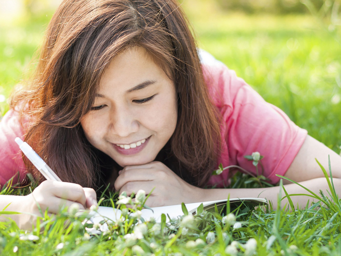 Photo of girl in the grass writing in a journal
