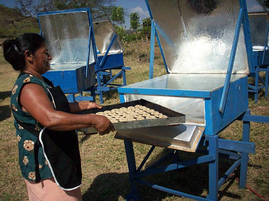Cooperative member Rumelda loads cookies into a solar cooker
