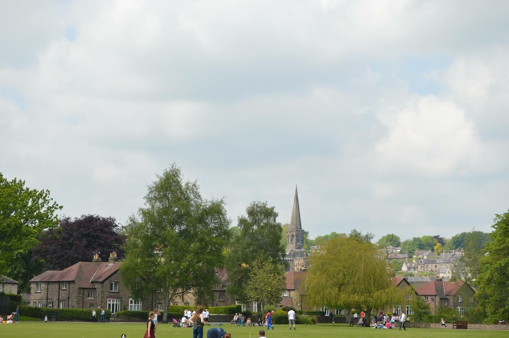 Lots of people enjoying the park with All Saint Church in the background.