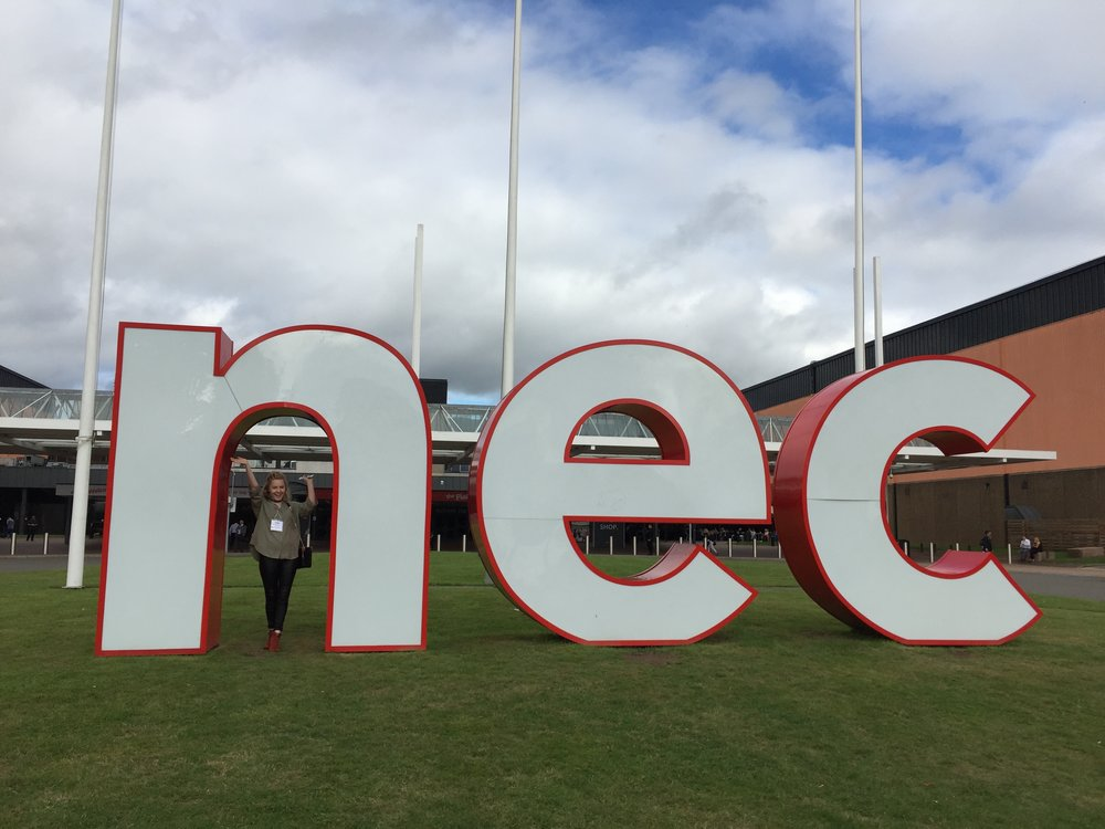 Rebecca with the NEC sign.