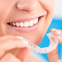 Photo of a smiling patient using Invisalign clear aligners at this dentist in Portland, OR