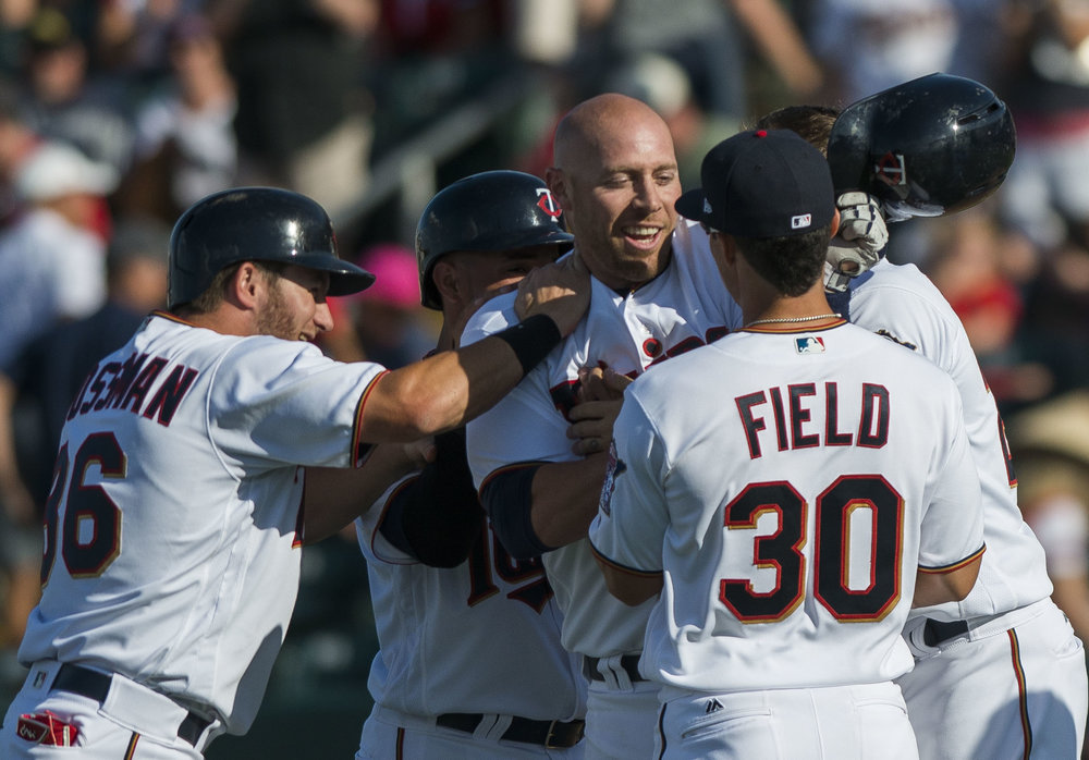 Teammates surround catcher Chris Gimenez after he batted a runner in for the winning score in the 10th inning in the game against St. Louis Cardinals on March 6 at Hammond Stadium.