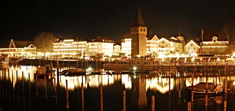 Bild: Der Lindauer Seehafen bei Nacht....funkelnd schön! Das zweite Haus rechts neben dem sogenannten Mangturm ist das Hotel Schreier.