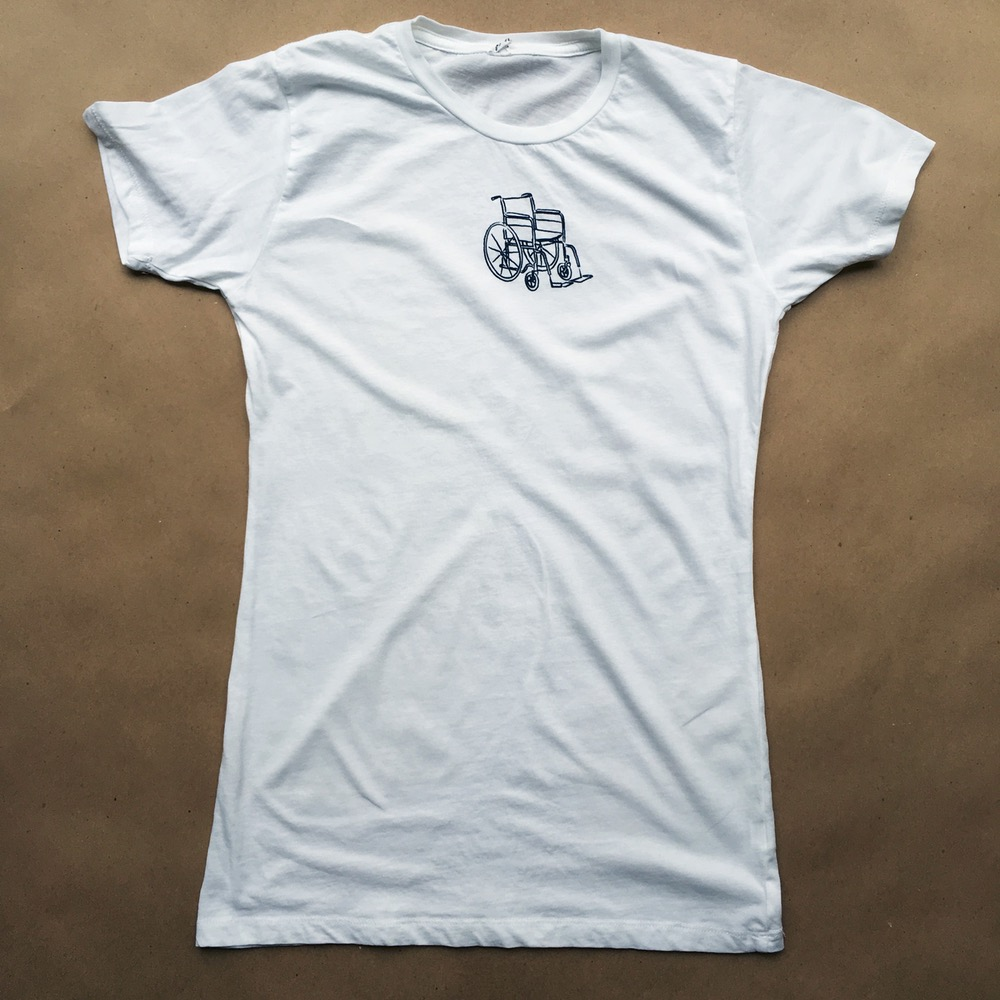 Pictured: White t-shirt with black wheelchair illustration in the center of the top half of the shirt.