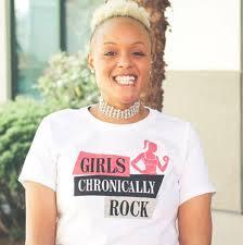 "Keisha Greaves smiles at the camera, wearing a ""Girls Chronically Rock"" shirt."
