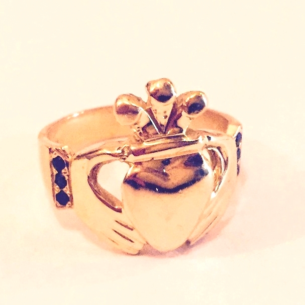 Men's 18K yellow gold claddagh ring with black diamond cuffs.
