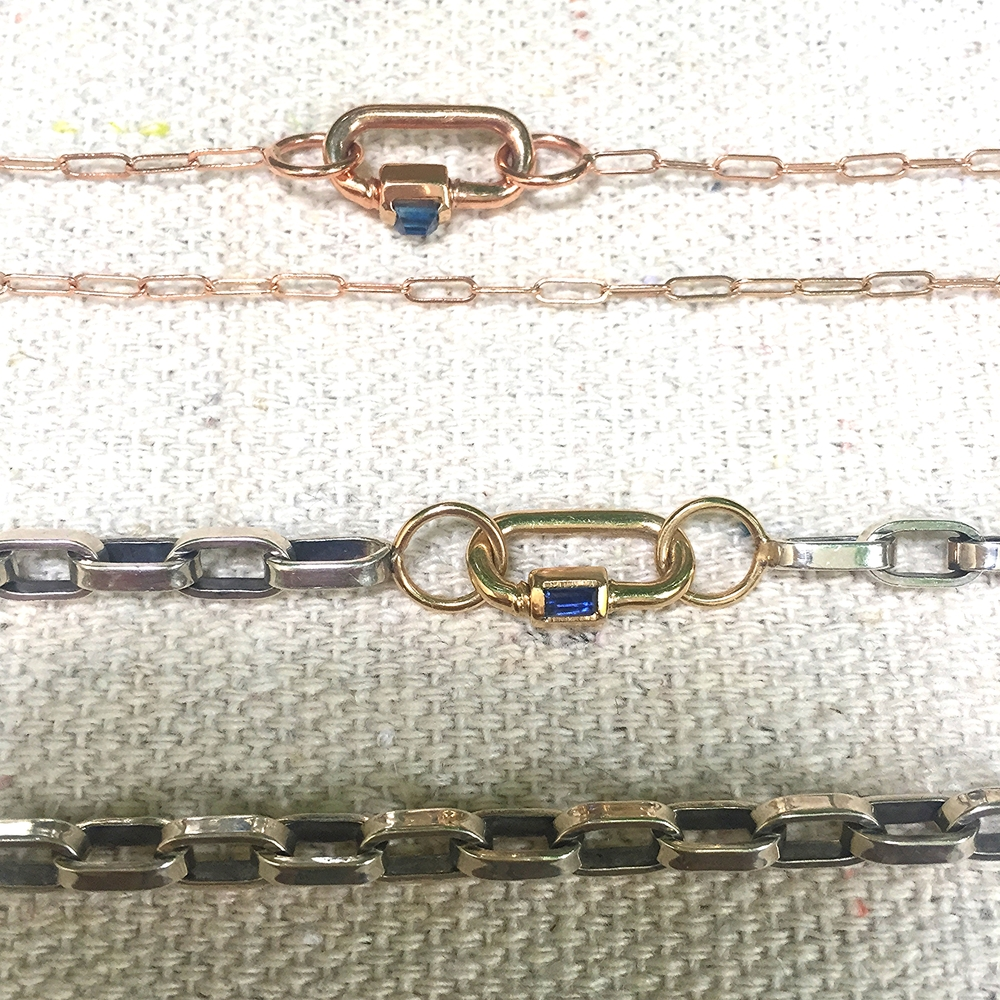 Mini locks with sapphires baguettes in 14K rose and yellow gold with varying thicknesses of chain options.