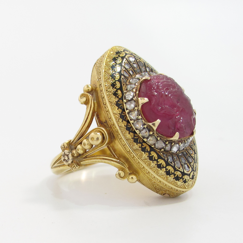 A mid-to-early-1800s poison ring with a carved ruby cameo, black enamel detailing and rose cut diamonds on the perimeter from Excalibur Jewelry.
