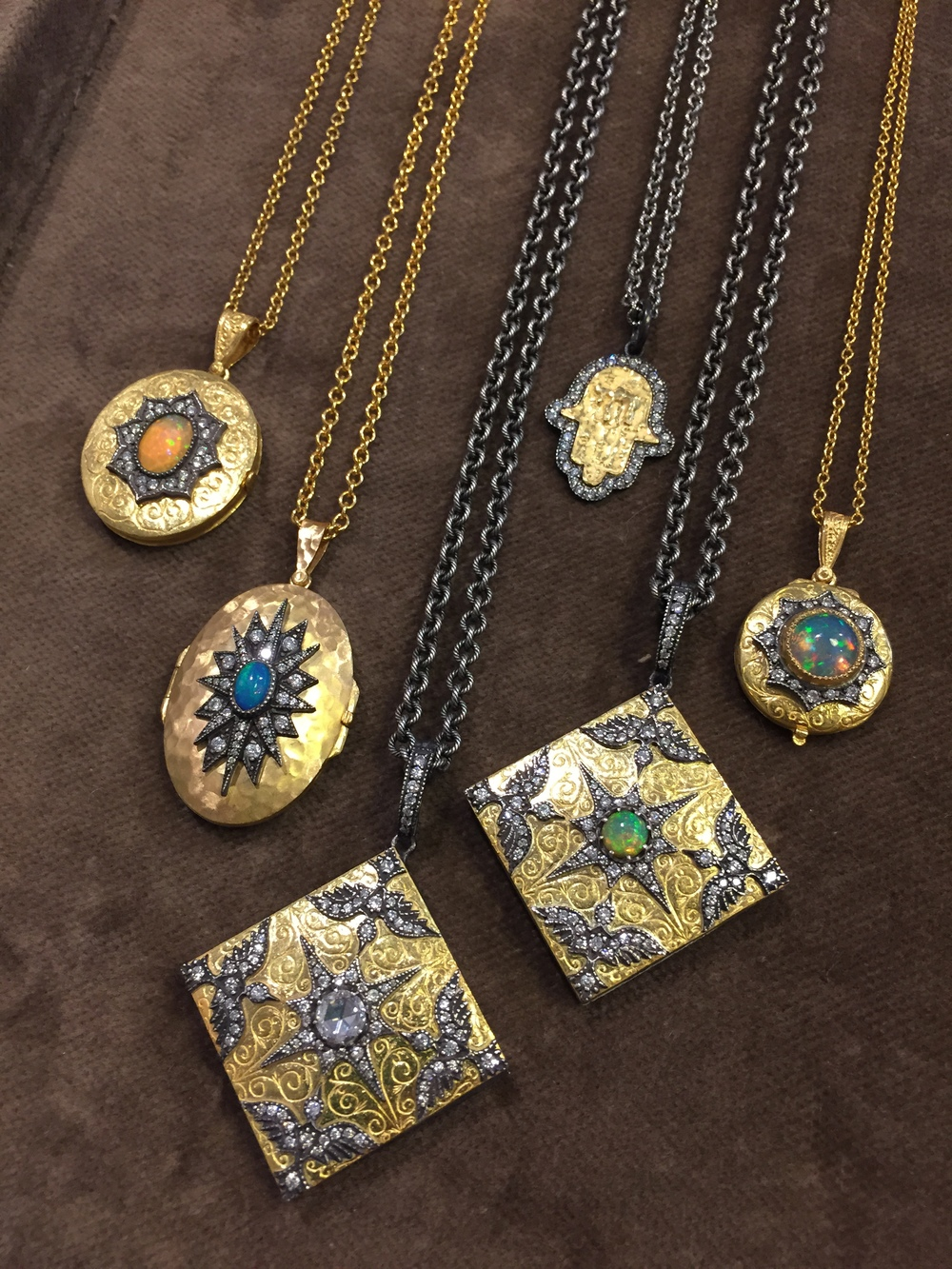 A selection of exceptional hand-carved 22k gold and silver lockets and pendants with gemstone and diamond accents, available at  Art & Soul , Boulder, CO.