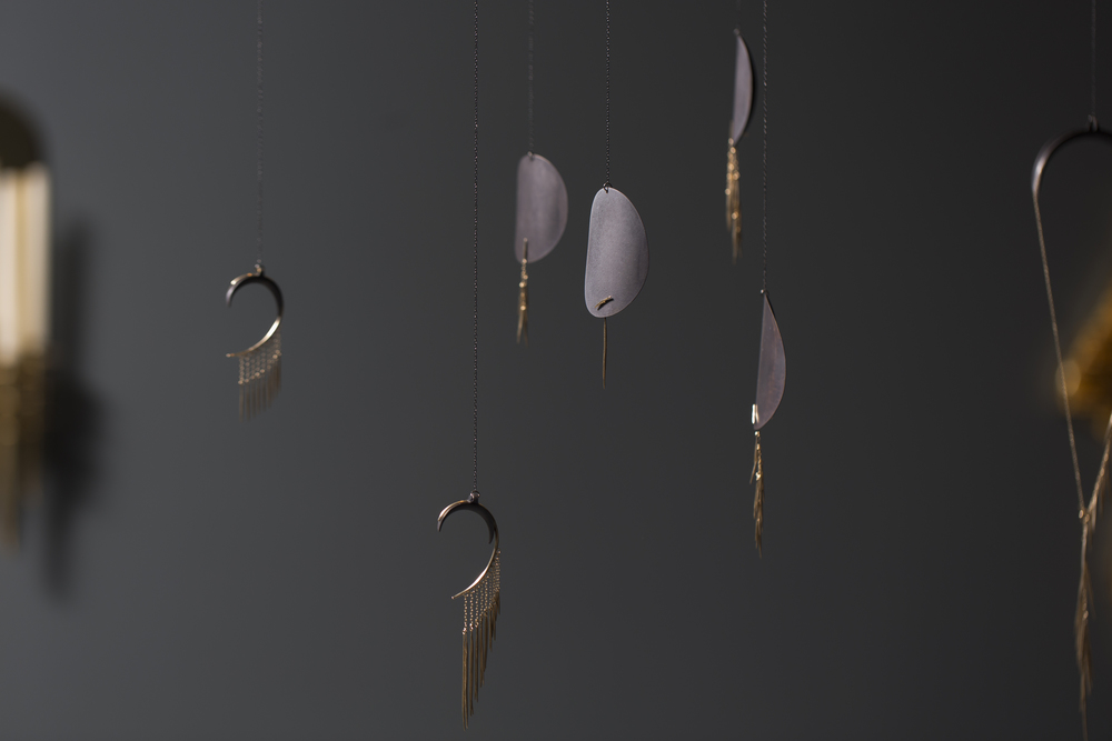 Fringy gold happy things displayed on leather forms. We want.