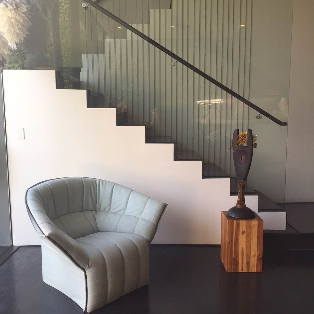 Modern furniture and sculptures by Jeff Wise are scattered around the three-story space.