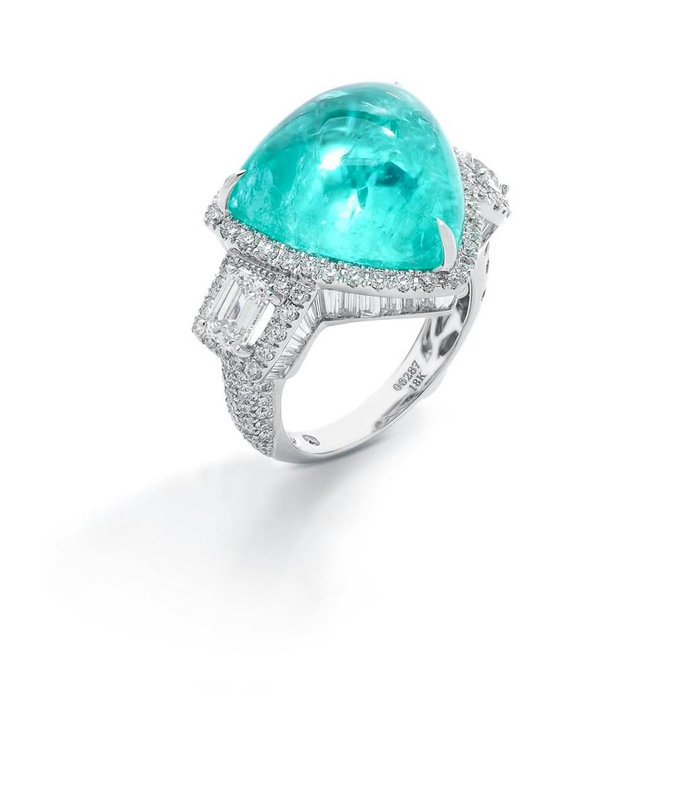 Trinity ring in 18k white gold with a 15.89 carat Paraiba tourmaline trillion and white diamonds.