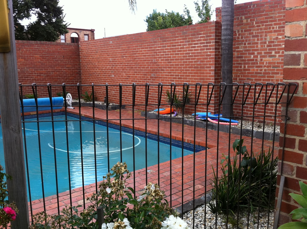Before - a tired, old pool - the brick paving was lifting, the pool tiles falling off, and a section of the high brick wall leaning precariously.