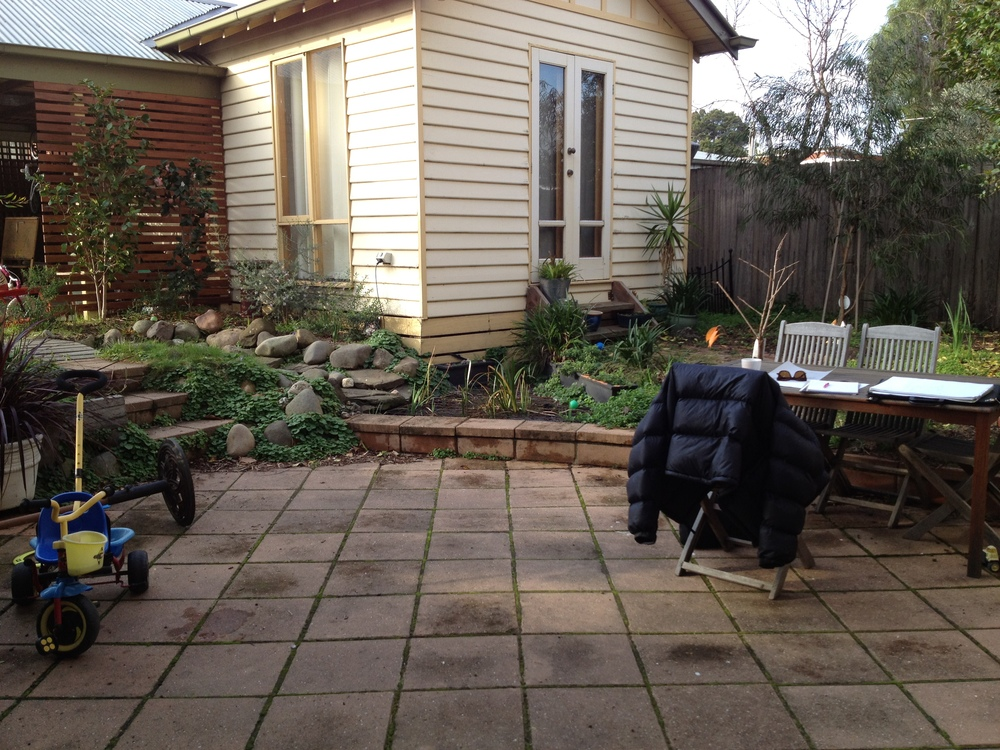 Before - a tired space, with slippery paving, no soft areas for play, and no distinct entertaining area or way to get to the bungalow.