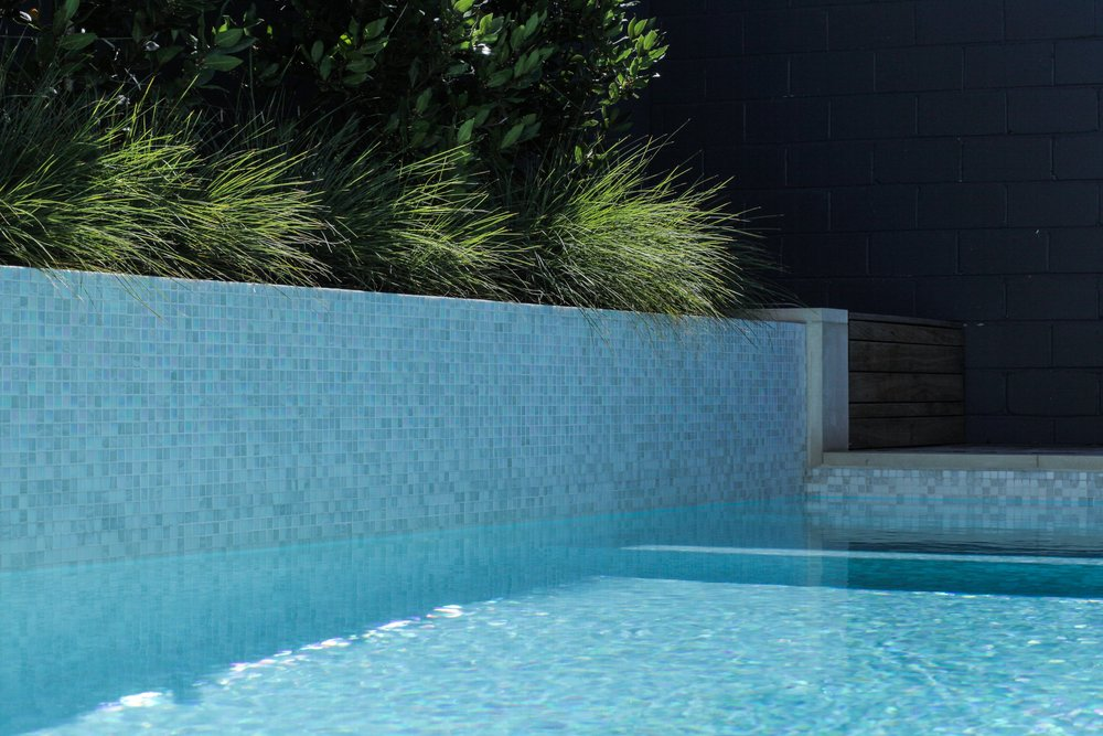 Mother-of pearl swimming pool tiles give the pool and spa extra shimmer - running them up an attached planter wall adds layers to give the area interest.