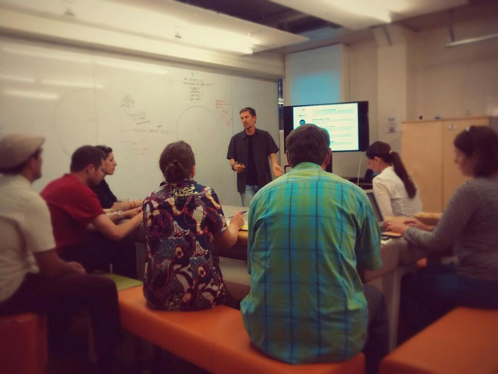 Michael Berry (standing) speaks with the d.school fellows during a studio session on Monday, May 12. (Emi Kolawole)