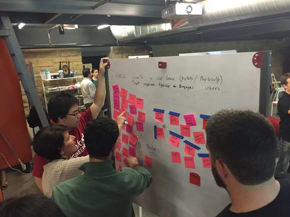 "A team populates a whiteboard with new ideas during class three of ""Redesigning the News Ecosystem."""