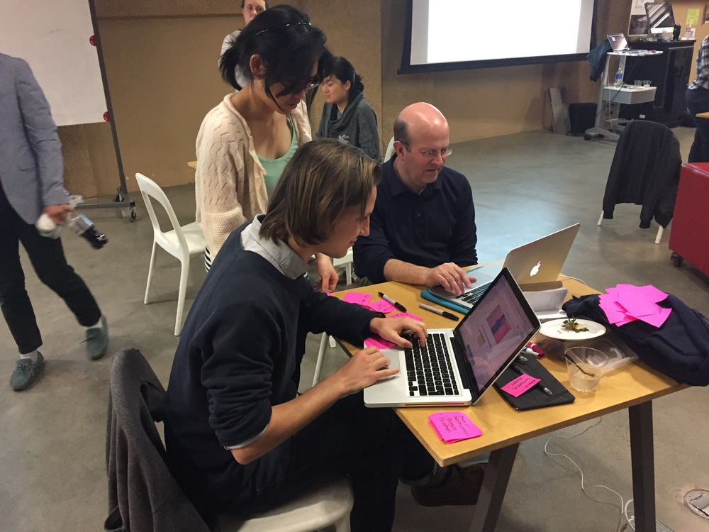 "Students work with Jay Hamilton, the Director of Stanford's Journalism Program, (right) testing ""Pink It"", one of the prototypes created during class. (Emi Kolawole)"