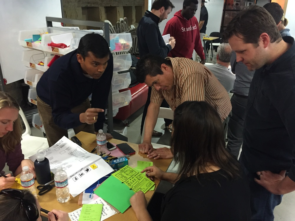 Jen Cotton (center) and Dave Wright (far right) test a prototype during the final class of Redesigning the News Ecosystem. (Emi Kolawole)