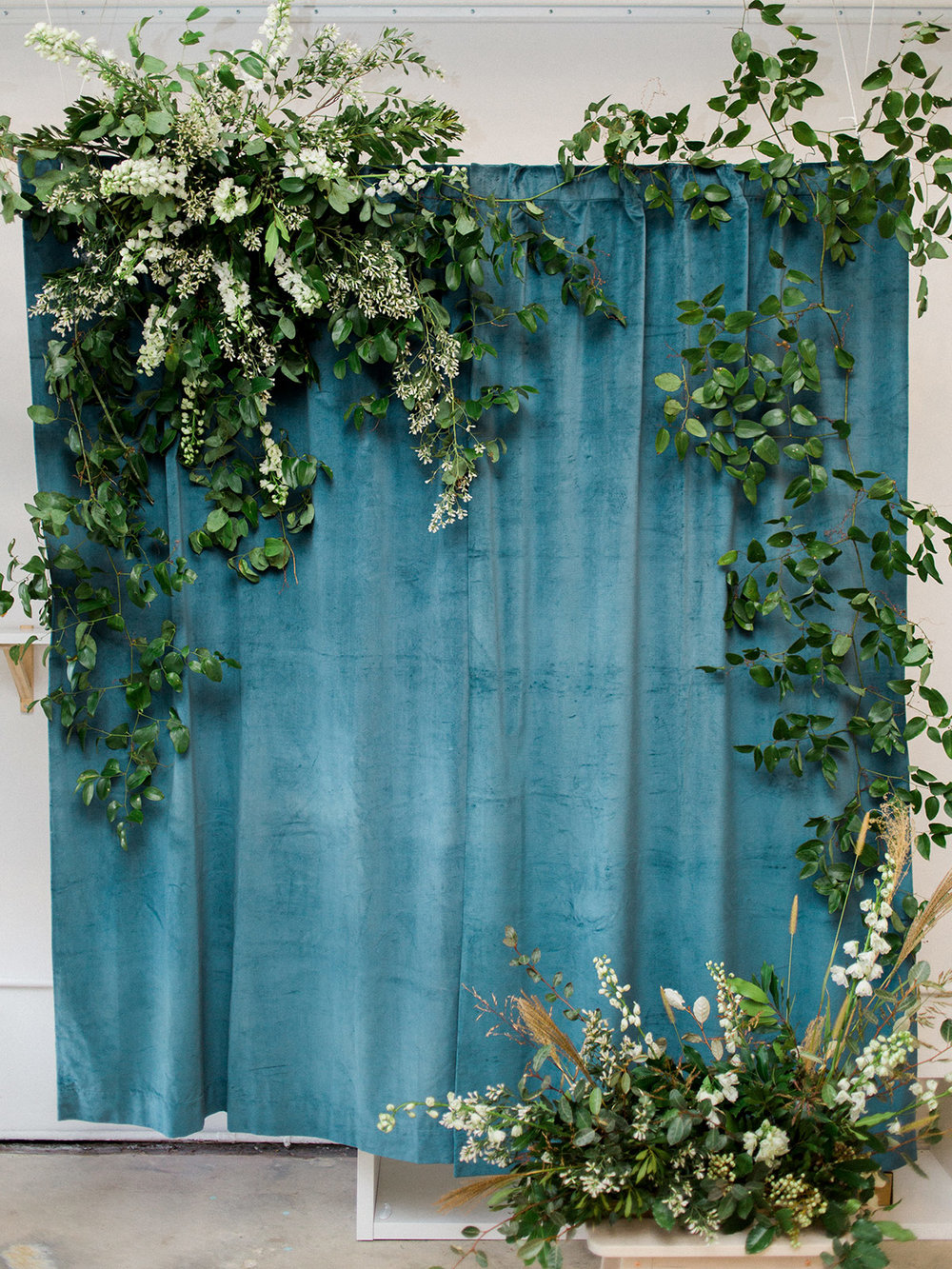 Our party backdrop. We love a good excuse to get on a ladder and hang some flowers.